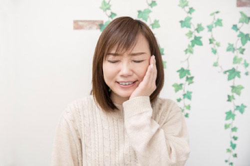 歯を抑える男性