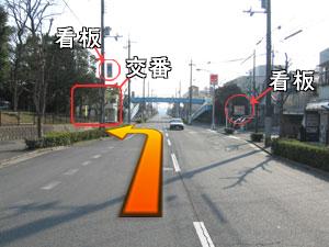 看板が見えてきます。左側の交番が目印です